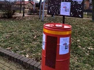 Czerwony metalowy okrągły pojemnik na plastikowe nakrętki na tle trawnika