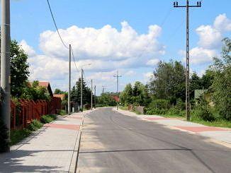 Asfaltowa ulica z wyknanym z kostki brukowej chodnikiem; wzdłuz niego latarnie