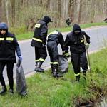 Strażacy wyciągają śmieci z przydrożnego rowu