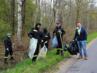 strażacy z workami śmieci w lesie