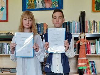 Dwoje młodych ludzi - dziewczyna i chłopak - stoją na tle regalu z książkami i trzymaja w dłoniach zaświadczenia, że są finalistami konkursu przedmiotowego