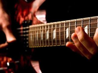 Dłoń na gryfie gitary