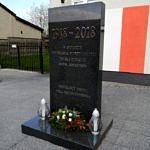 Pomnik z wiązanką kwiatów i dwoma zniczami