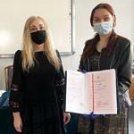 Przedstawiciele szkoły wręczają dyplomy i świadectwa uczniom - na zdjęciu dziewczyna ze świadectwem z czerwonym paskiem
