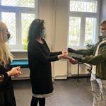 Przedstawiciele szkoły wręczają dyplomy i świadectwa uczniom