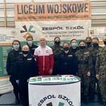 Wicemistrz Europy w Zapasach Mateusz Bernatek w Biało-czerwonym dresie stoi w otoczeniu młodzieży z klasy policyjnej i wojskowej w mundurach