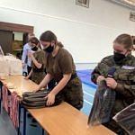 Dziewczęta w maskach rozkładadaja nagrody - plecaki i medale