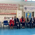 Bernatek, przedstawiciele szkoły w Gomulinie, samorządowcy i radni siedzą prz drabinkach na tle plakatów promocyjnych