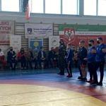 Zawodnicy i obserwatorzy stoją na sali