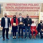 Organizator Tomasz Woźniak wręcza podziękowania przedstawicielom szkoły i gminy