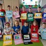 Grupa dzieci, które trzymają w rękach wykonane z kartonów laptopy