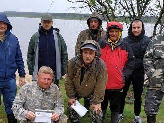 Grupa wędkarzy (część z dyplomami) nad zbiornikiem wodnym