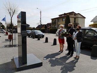 Delegacja 3 osób - przewodnicząca RG Małgorzata Gniewaszewska, wójt Roman Drozdek i radna Agata Szmalec składają wiązankę kwiatów przed pomnikiem