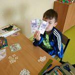 Dziecko nad stołem z banknotami i wyciętymi z papieru monetami