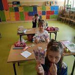 Dzieci nad stołem z banknotami i wyciętymi z papieru monetami