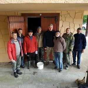 Grupa wędkarzy stojąca na tle domku w Wygodzie