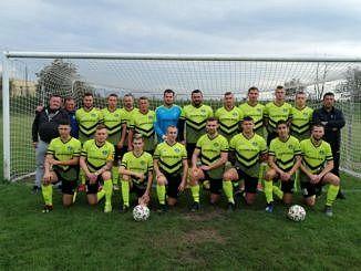 drużyna piłkarska w seledynowych strojach na tle bramki