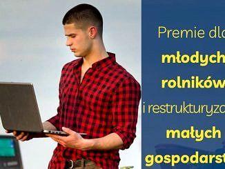 Młody mężczyzna w kraciastej koszuli trzyma laptopa; wszystko na tle pola i ciągnika