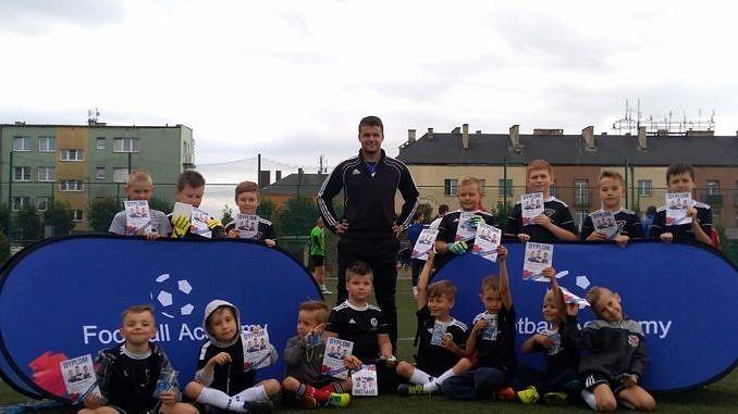 Młodzi piłkarze siedzą przed niebieskim banerem Footbaal Academy; po środku stoi trener w czarnym dresie