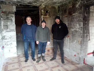 W zniszczonym wnętzu stoją trzej mężczyźni