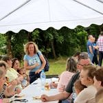 Mieszkańcy Mąkolic pod zadaszenim na powietrzu przy stole z przekąskami