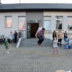 Dzieci z opiekunami podczas zabaw i animacji - dorosły skacze przez skakankę kręconą przez dzieci
