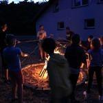 Ludzie przy ognisku podczas pieczenia kiełbasek o zmroku