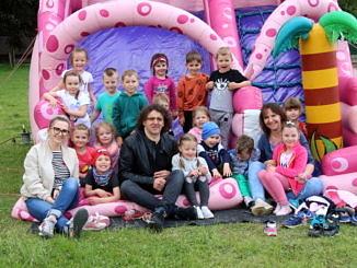 Grupa dzieci z opiekunami sziedzi na różowej dmuchanej zjeżdżalni