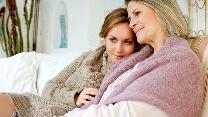 Dwie kobiety - starsza i młodsza siedzą przytulone do siebie