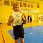Chłopiec w niebieskim stroju zapaśniczym z medalem; w ręce trzyma dylom za zjęcie III miejsca