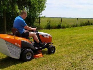 Człowik kosi boisko kosiarką samojezdną (traktorkiem)
