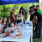 Ludzie posilający sie przy stole piknikowym