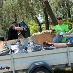 Mężczyźni rozładowuj śmieci z przyczepki
