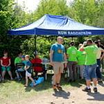 grupa osób - część w seledynowych koszulkach Leszy - stoi na tle niebieskiego zadaszenia z napisem KGW Radziątków