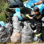 Sterta śmieci w workach plus opony i telewizor i mały strażak pomaga je układać