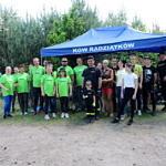 Duża grupa osób - część w seledynowych koszulkach Leszy - stoi na tle niebieskiego zadaszenia z napisem KGW Radziątków
