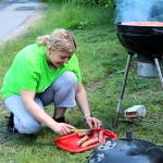 Kobieta przygotowuje kiełbaski na grill
