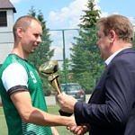 Kapitan LZS OSP Gomulin w zielonej koszulce odbiera puchar z rak wójta gminy Romana Drozdka
