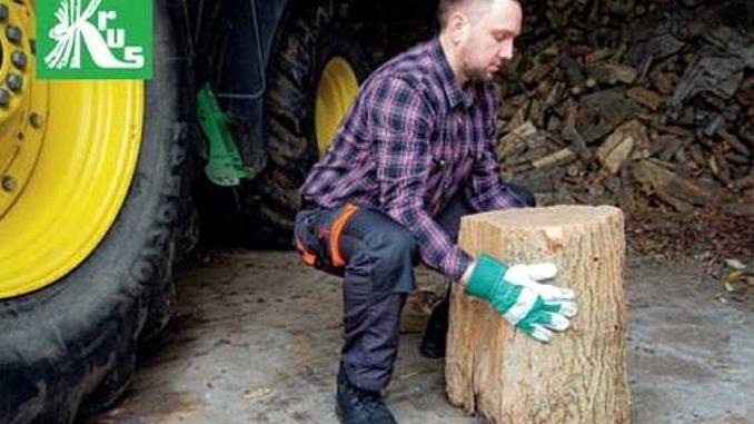 rolnik na tle ciągnika kuca i dźwiga pień drewna