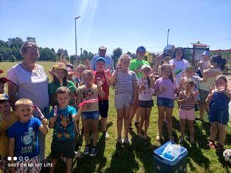 Grupa dzieci z opiekunami i przewodniczącą Rady Gminy Wola Krzysztoporska z nagrodami podczas pikniku