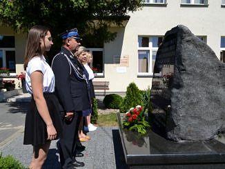 Delegacja szkoły - uczniowie dyrektorka i strażak składają kwiaty przed tablicą upamiętniającą Lecha Kaczyńskiego