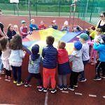 Dzieci z animatorkami podczas gier i zabaw na orliku - z kolorową chustą