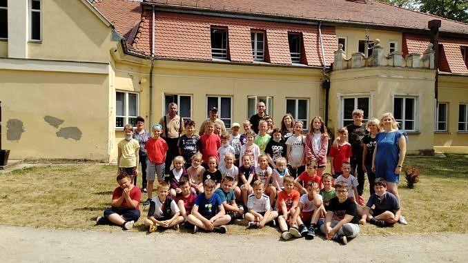 Grupa dzieci z nauczycielami przed szkołąw Parznirwicach