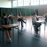 Uczniowie przy stolikach podczas testu