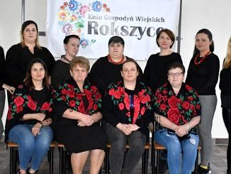 Członkinie KGW Rokszye w ciemnych strojach z zarzuconymi chustami w czerwone kwiaty siedzą i stoją pod banerem KGW