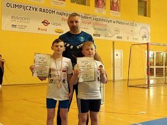 Dwaj chłopcy z trenerem trzymaja rękch dyplomy