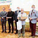 Nagrodzony stoi z upominkami w otoczeniu organizatorów konkursu