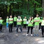 Grupa ludzi (część w zielonych koszulkach Leszy) przygotowuje się do wyjścia w teren
