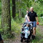 Grupa ludzi (część w zielonych koszulkach Leszy) sprząta las - na pierwszym planie mężczyzna z dzieckiem w wózku