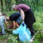 Grupa ludzi (część w zielonych koszulkach Leszy) sprząta las